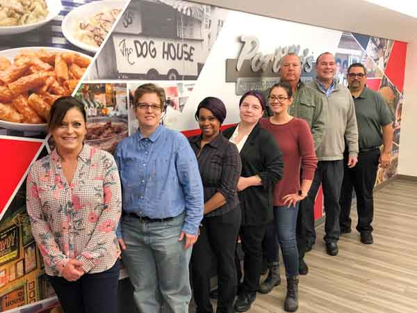 Portillo's Team Poses With Wall Graphics During Training.
