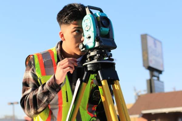 Surveyor uses laser scanning on a job site.